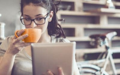 Chica joven bebiendo un cafe y mirando su libreta
