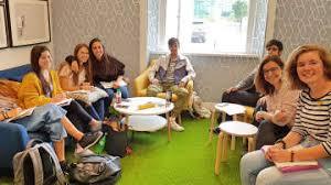 Grupo mixto de personas de joven edad sentadas en una sala, con mesas redondas y posando para la camara