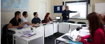 Grupo de estudiantes en una clase de Ingles, con el maestro delante de una pantalla y los alumnos mirando