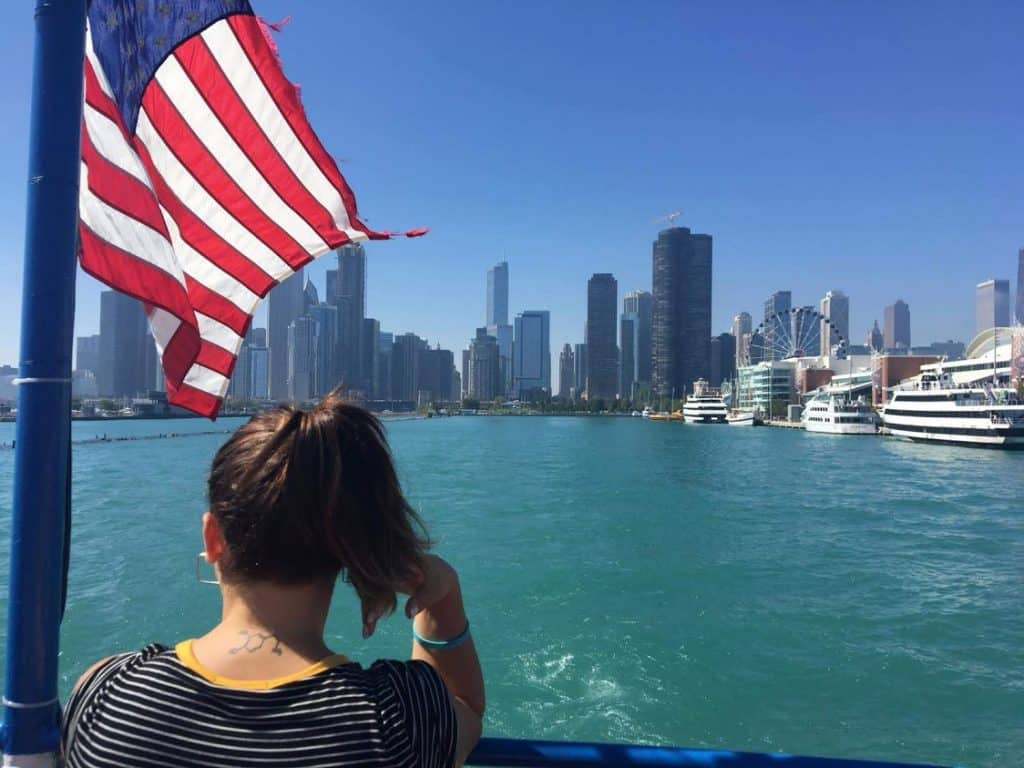 au pair mirando la ciudad con bandera de estados unidos
