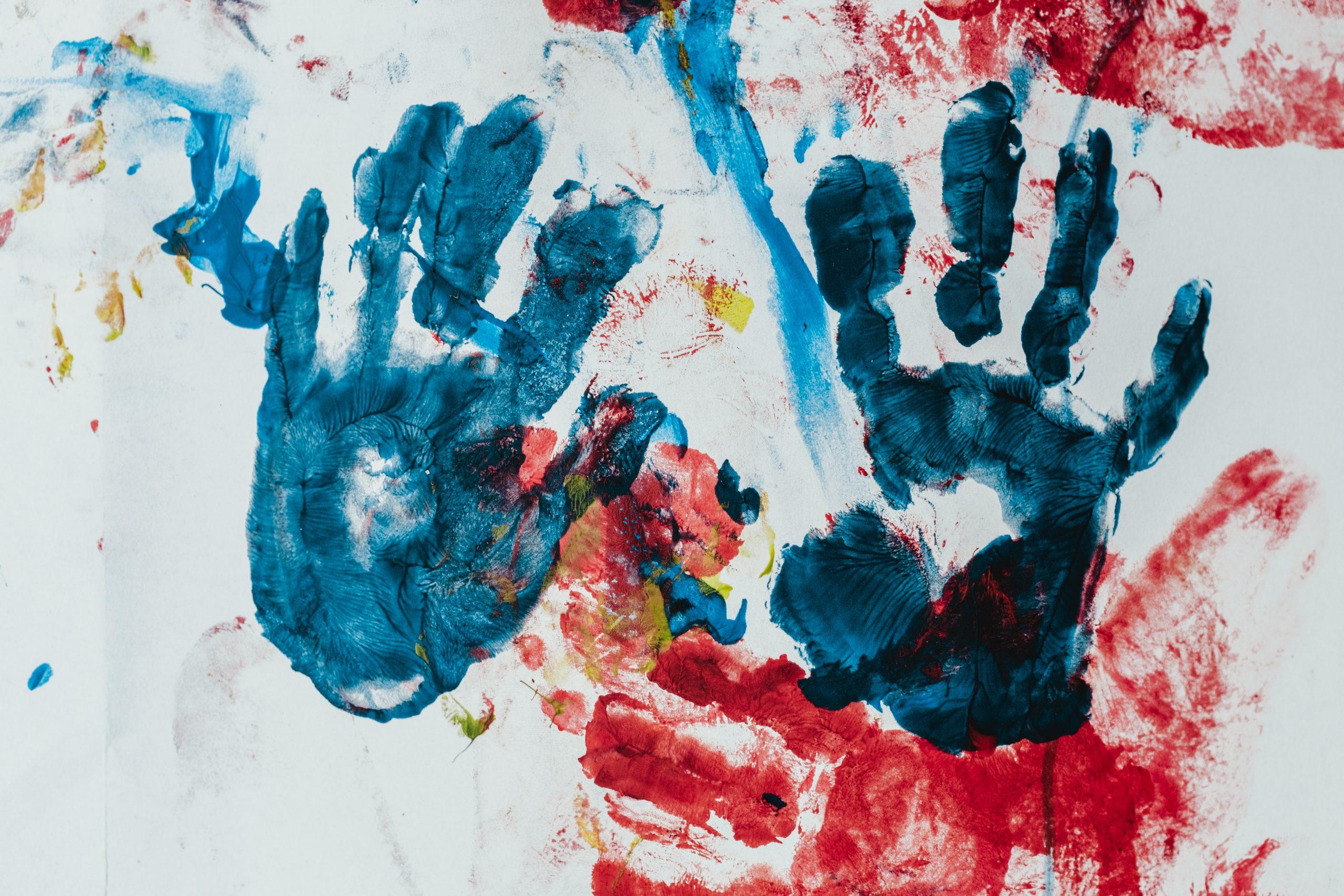 Manos de niños con pintura sobre papel