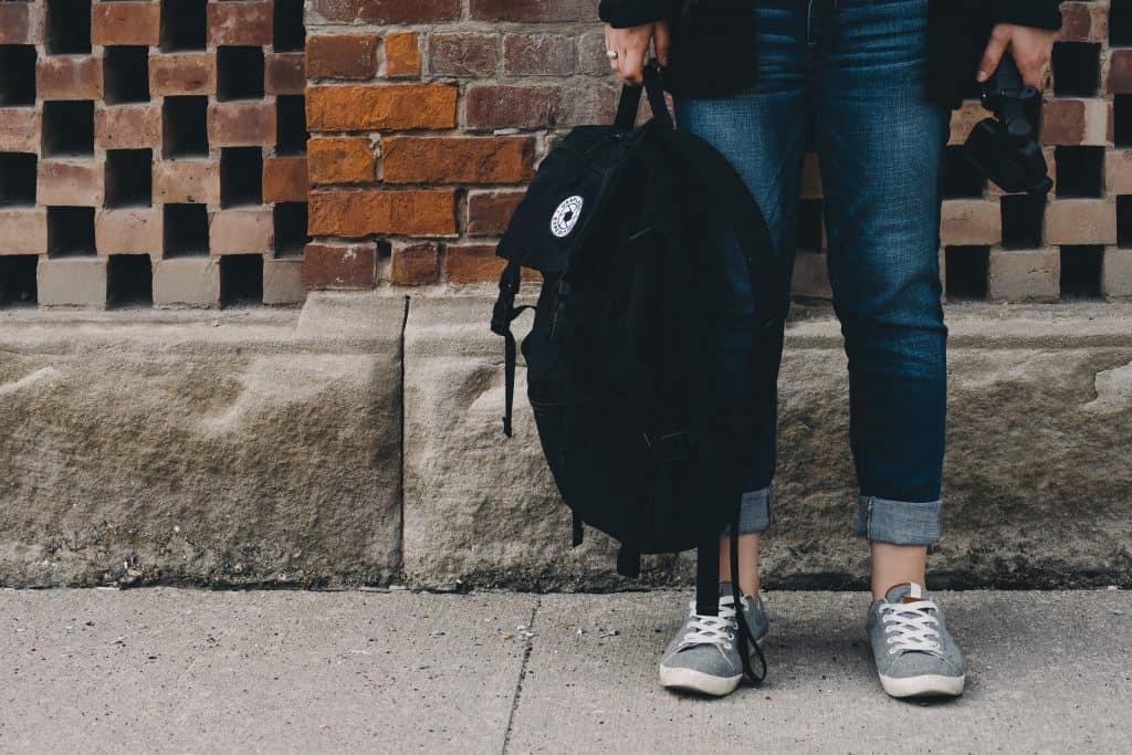 mujer joven sosteniendo mochila