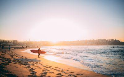 playa de australia, persona con tabla de surf mirando el mar al atardecer