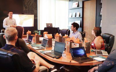mesa de trabajo, personas sentadas alrededor con sus computadoras y una persona parada exponiendo. pasantías