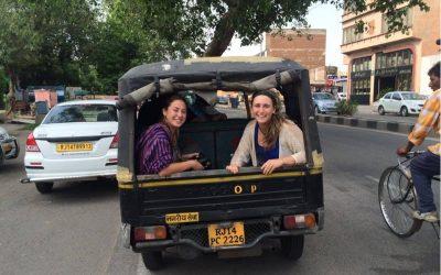 dos mujeres sonriendo en el baúl de una camioneta en india