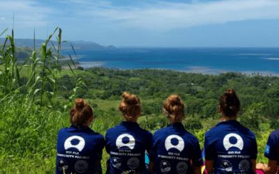 voluntarios de espaldas senatados sobre colina mirando el mar. desarrollo sostenible