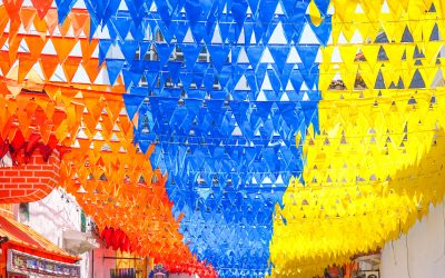 calle en colombia coon banderines rojos, azules y amarillos colgando arriba