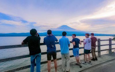 amigos apoyados sobre baranda observando el mont fujimori. pasantías