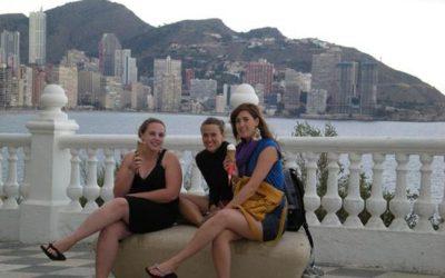 tres mujeres sentadas tomando vino con fondo de mar y la ciudad de alicante