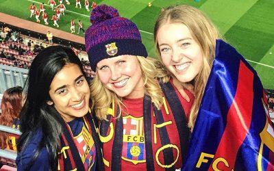 tres mujeres con remeras del Barça y bufandas y gorros en la cancha de futbol