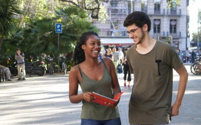 una mujer y un hombre riendose con libro en la mano en las calles de barcelona. semestre en el extranjero