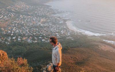 hombre mirando el horizonte parado sobre una piedra con ciudad del cabo a lo lejos. secundaria en sudáfrica
