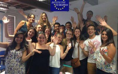 alumnos de curso de italiano festejando con las manos en alto