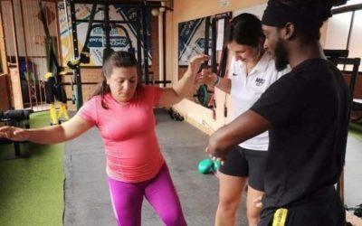 mujer haciendo ejercicios con dos fiioterapuetas ayudando