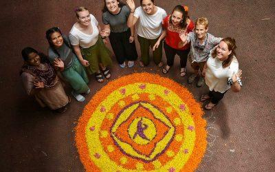 mujeres sonriendo para arriba con dibujo de mandala en el piso. desarrollo de comunidades