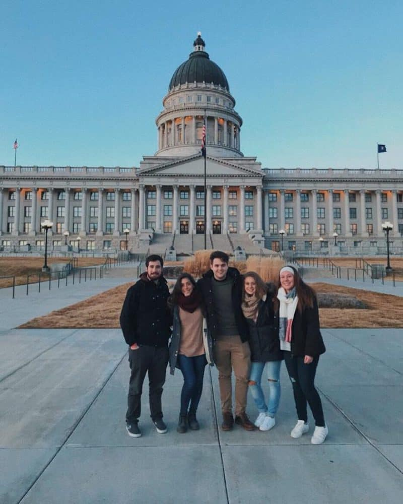 cinco amigos abrazandose frente al capitolio en washington. work and travel