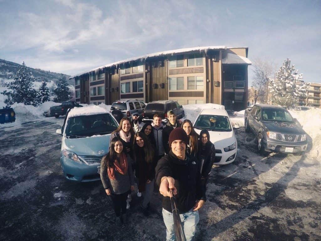 grupo de amigos tomándose selfie en la nieve, con autos detras y casa de madera