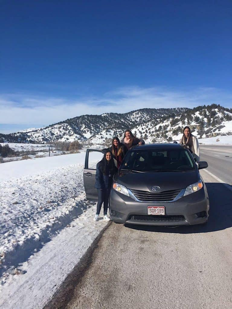 cuatro amigas en auto, en la ruta rodeadas de paisaje montañoso y nevado.