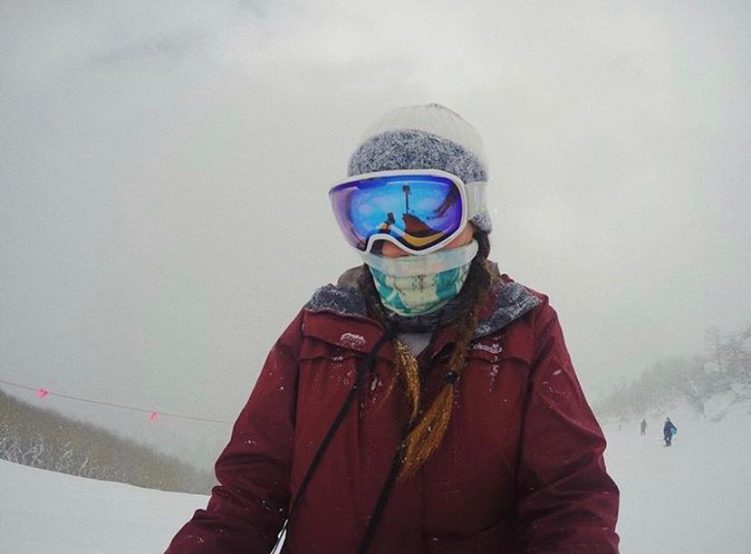 mujer vestida con ropa de sky, antiparras, gorro y campera. en la nieve. work and travel