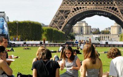 jovenes almorzando un pic nic frente a la torre eiffel. estudiar en paris