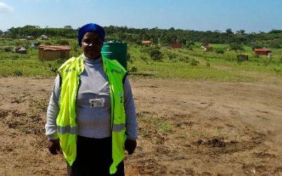 mujer con chaleco fluorescente parada con fondo rural. atención médica domiciliaria