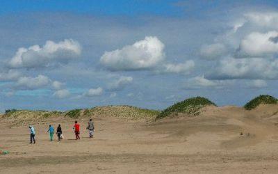personas caminando a lo lejos en desierto de arena y pasto