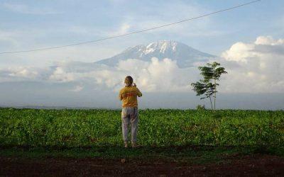 mujer con remera amarilla tomando foto de montaña parada sobre tierra