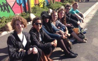 jovenes sentados sobre el cordón de la calle