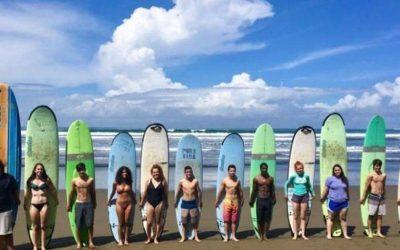adolescentes con tabla desurf detras en la playa. viaje de aventura