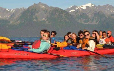 jovenes en kayaks en rio en alaska con montañas de findo
