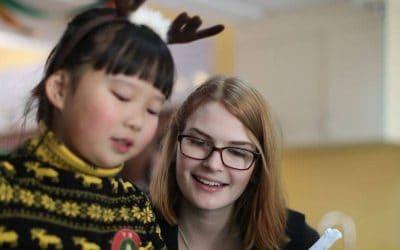 mujer con anteojos con niña con vincha de cuernos