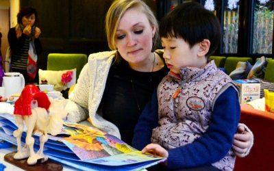 mujer sosteniendo niño en sus faldas mirando libro