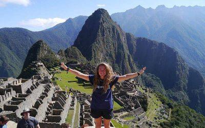 mujer parada con brazos abiertos, en la cima de machu picchu