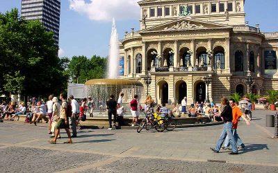 edificio historico en frankfurt con plaza enfrente y fuente de agua, personas paseando