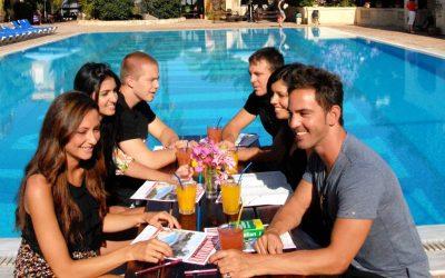 amigos sentados en la mesa con pileta detras