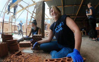 mujer sentada en el piso trabajando en la construcción. voluntariado en construcción
