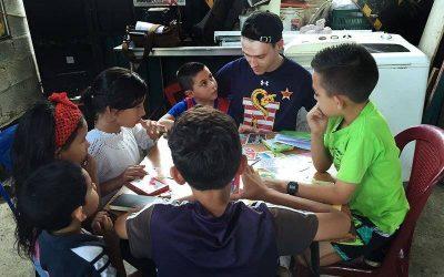 hombre joven enseñando a cuatro niños