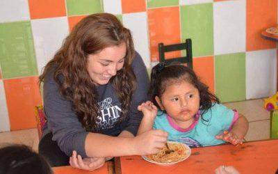 mujer joven ayudando a niña