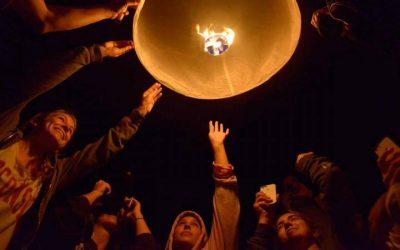 jovenes extendiendo mano para levantar lampara flotante- estudiar en tailandia