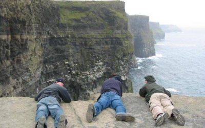 tres personas acostadas en el piso sobre precipicio y montañas y mar en el fondo