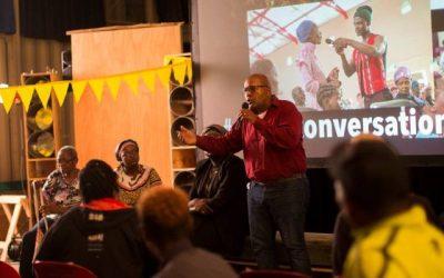 hombre con camisa roja hablando con microfono y pantalla de cine detras
