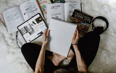 mujer escribiendo en cuaderno sin renglones y libros desparramados