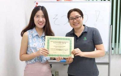 dos mujeres agarrando certificado de enseñanza