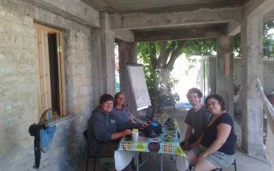cuatro personas reunidas alrefedor de mesa sonriendo