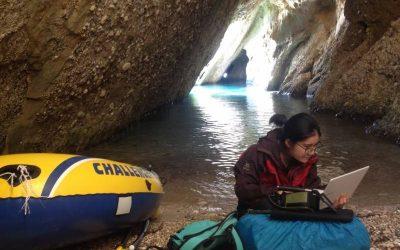 mujer escribiendo en computadora en cueva con bote amarillo al lado. voluntariado de campo